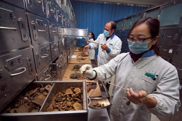 เจ้าหน้าที่การแพทย์แผนจีน ในโรงพยาบาลเมืองเซียงหยัง มณฑลหูเป่ย ขณะตวงวัดปริมาณสมุนไพรต่างๆ เพื่อปรุงยาแผนจีนโบราณ (แฟ้มภาพไชน่าเดลี)