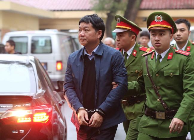 อดีตสมาชิกโปลิตบูโรพรรคคอมมิวนิสต์เวียดนามและอดีตประธานบริษัทปิโตรเวียดนาม นายดิง ลา ทัง (ซ้าย) ถูกควบคุมตัวขึ้นศาลในกรุงฮานอย. -- Reuters/VNA/Doan Tan.