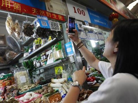 ลูกค้ากำลังจ่ายเงินโดยใช้มือถือสแกน QR code รับเงินของแม่ค้าในตลาดสด(ภาพ เอเจนซี่)