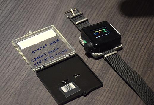 แก็สเซนเซอร์ที่ที่พิมพ์จากหมึกนำไฟฟ้าผสมอนุภาคนาโน (ในกล่อง)  และนาฬิกาแจ้งเตือนก๊าซพิษตัวต้นแบบ