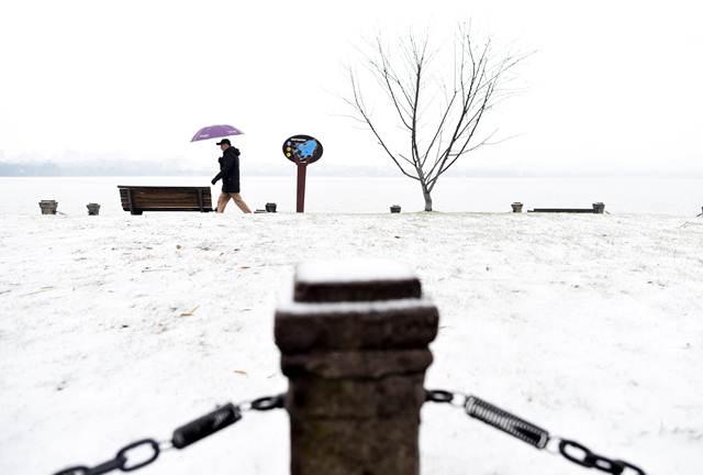 นักท่องเที่ยวเดินอยู่ในบริเวณทะเลสาบซีหู เมืองหังโจว มณฑลเจ้อเจียง ภาพ 25 ม.ค. (ภาพ ซินหวา)