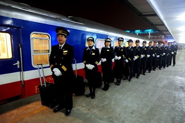 ผู้ควบคุมขบวนรถไฟและผู้ให้บริการบนรถไฟสายเหนือ-ใต้ ยืนเข้าแถวเตรียมพร้อมก่อนให้บริการผู้โดยสาร. -- ภาพ : ThanhnienNews.