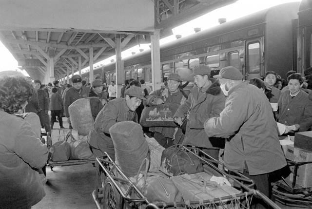 เจ้าหน้าที่ดูแลบริการผู้โดยสารช่วยเหลือผู้โดยสารหิ้วกระเป๋าสัมภาระที่สถานีรถไฟนครเซี่ยงไฮ้ แฟ้มภาพ ม.ค. 1983 -ซินหวา