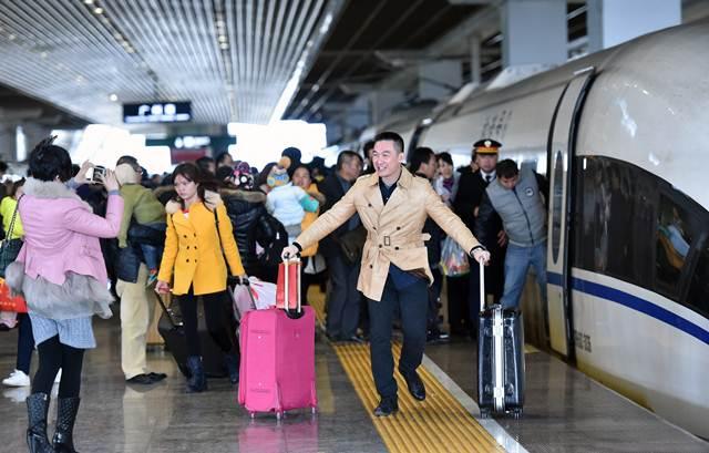 ผู้โดยสารจัดท่าทางถ่ายภาพกับรถไฟหัวกระสุนที่สถานีรถไฟกว่างโจวทิศใต้ ภาพ 24 ม.ค.2016 –ซินหวา