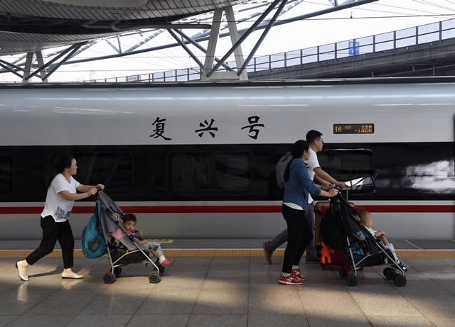 """ผู้โดยสารกำลังขึ้นรถไฟหัวกระสุน """"ฟู่ซิง"""" ที่สถานีรถไฟกรุงปักกิ่ง ซึ่งจะไปยังเซี่ยงไฮ้ ทั้งนี้ จีนเปิดบริการรถไฟความเร็วสูงในเส้นทางปักกิ่ง-เซี่ยงไฮ้เมื่อ 6 ปีที่แล้ว แต่ได้ลดความเร็วลงมาที่ 300 กม./ชม.ซึ่งใช้เวลาเดินทางราว 5 ชม. (ภาพ ซินหวา)"""