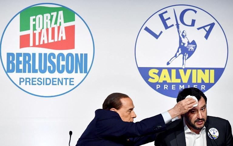 """<i>(ภาพจากแฟ้ม) อดีตนายกรัฐมนตรีอิตาลี ซิลวิโอ แบร์ลุสโกนี ซึ่งเป็นผู้นำของพรรคฟอร์ซา อิตาเลีย ที่มีแนวทางกลาง-ขวา (ซ้าย) ใช้ผ้าเช็ดหน้าผากของ  มัตเตโอ ซัลวินี ผู้นำกลุ่ม """"ลีก"""" ที่มีแนวทางขวาจัด  ขณะเขาปล่อยมุกตลกบนเวทีแถลงข่าวร่วม ในกรุงโรม เมื่อวันที่ 1 มี.ค. ที่ผ่านมา  ทั้งนี้ผลการเลือกตั้งอิตาลีเมื่อวันอาทิตย์ (4 มี.ค.) ชี้ว่า แนวร่วมฝ่ายขวาซึ่งมีทั้งสองพรรคเป็นแกนนำ  ได้คะแนนมากกว่าพรรคหรือกลุ่มแนวร่วมอื่นๆ  ขณะที่ภายในแนวร่วมนี้ """"ลีก"""" ได้เสียงมากกว่า """"ฟอร์ซา อิตาเลีย""""  จนพูดกันว่า ซัลวินีอาจได้เป็นนายกฯอิตาลีคนต่อไป </i>"""
