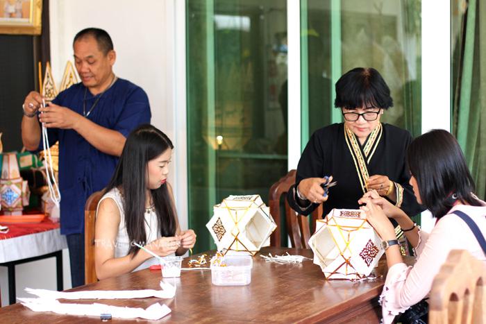 นักท่องเที่ยว(นั่ง)ทดลองทำโคมมะเต้าที่บ้านโคมคำ