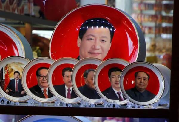 จานที่ระลึกภาพอดีตผู้นำจีน และผู้นำคนปัจจุบัน ทั้ง สี จิ้นผิง และประธานเหมา เจ๋อตงผู้ล่วงลับ ในร้านขายของที่ระลึก ในกรุงปักกิ่ง ภาพ 1 มี.ค. 2018 (ภาพ รอยเตอร์ส)