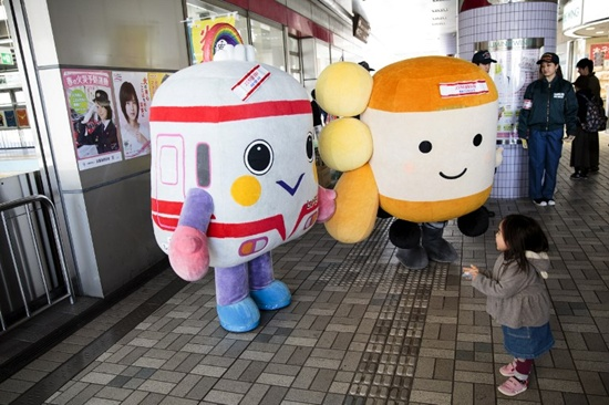 In this photo taken on March 3, 2018, a Japanese girl looks at railway mascots at a train station in Kamakura, Kanagawa prefecture. Japan has thousands of larger-than-life puppets with cutesy but improbable features, which are used to promote everything from regional attractions to public safety messages. Behrouz Mehri/AFP