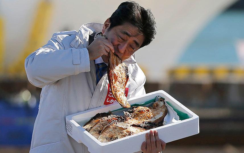ภาพเมื่อเดือนธันวาคม 2557 นายกรัฐมนตรีชินโซ อาเบะแห่งญี่ปุ่นลองชิมปลาย่างระหว่างหาเสียงในจังหวัดฟูกูชิมะ