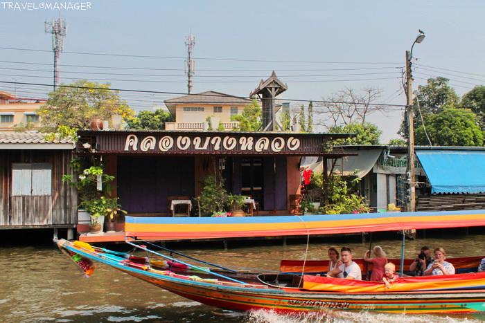 นักท่องเที่ยวชาวต่างชาติที่นั่งเรือชมวิถีชีวิตริมคลอง