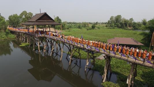 ชาวสารคามตักบาตรพระสงฆ์ 235 รูปบนสะพานไม้เกาะเกิ้ง วันพระราชสมภพสมเด็จพระเทพฯ