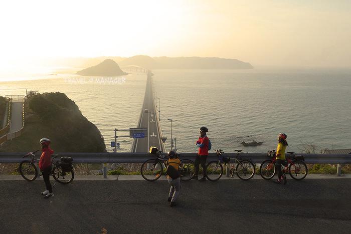 คณะนักปั่นเพลิดเพลินกับการถ่ายรูปสะพานทสึโนชิมะยามเย็น
