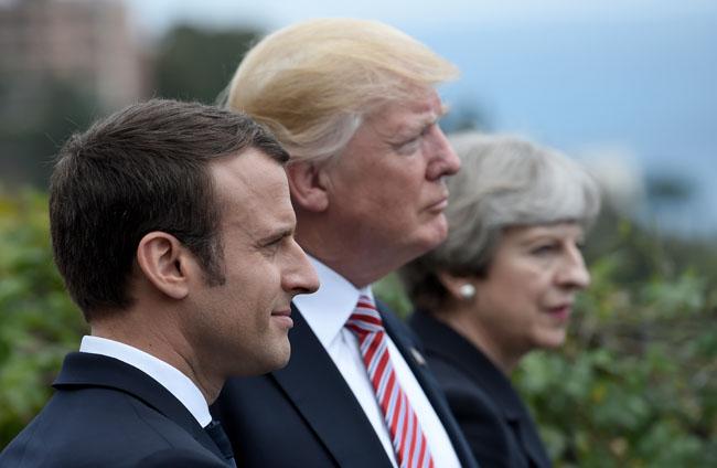 แฟ้มภาพ (จากซ้ายไปขวา) นายเอมมานุเอล มาครง ประธานาธิบดีฝรั่งเศส นายโดนัลด์ ทรัมป์ ประธานาธิบดีสหรัฐฯ และนางเทเรซา เมย์ นายกรัฐมนตรีอังกฤษ 3 ชาติที่จับมือกันใช้กำลังทหารเข้าโจมตีซีเรีย