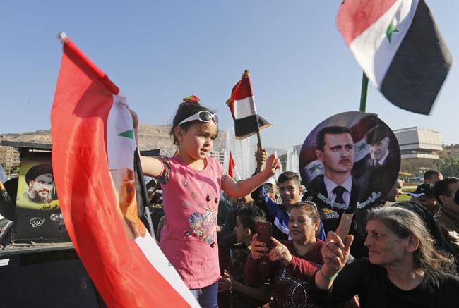 ชาวซีเรียโบกธงชาติซีเรียและภาพของประธานาธิบดีบาชาร์ อัล-อัสซาด ระหว่างการรวมตัวกัน ณ จัตุรัสอุมัยยัด ในกรุงดามัสกัส ในวันนี้ (14) เพื่อประณามการโจมตีของสหรัฐฯ อังกฤษ และฝรั่งเศส