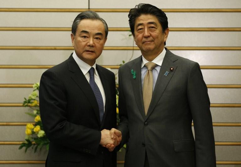 <i>มนตรีแห่งรัฐและรัฐมนตรีต่างประเทศ หวัง อี้ ของจีน (ซ้าย) จับมือกับนายกรัฐมนตรีชินโซ อาเบะ ของญี่ปุ่น ขณะเข้าเยี่ยมคำนับที่ทำเนียบนายกรัฐมนตรีในกรุงโตเกียว เมื่อวันจันทร์ (16 เม.ย.) </i>