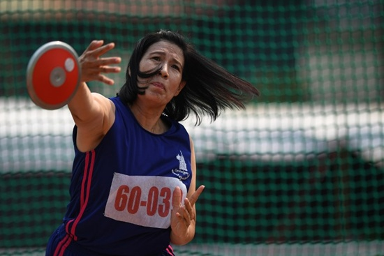 This photo taken on April 25, 2018 shows a woman in the 60-65 age category competing in the discus throw during Thailands first national Elderly Games in the northern Thai province of Nan. Lillian Suwanrumpha/AFP
