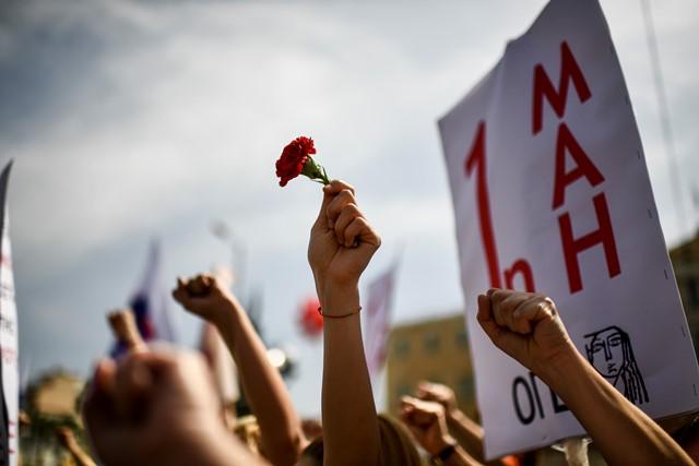 สมาชิกของสหภาพแงงานคอมมิวนิสต์กรีก (PAME) ชูดอกคาร์เนชั่นในระหว่างการเฉลิมฉลองวันแรงงานในกรุงเอเธนส์ (1 พ.ค.)