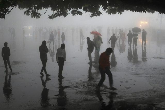 ภาพเมื่อวันที่ 2 พฤษภาคม ปี 2018 เผยให้เห็นคนกำลังเดินท่ามกลางฝนตกหนักในเมืองชิมลาในรัฐหิมาจัลประเทศ