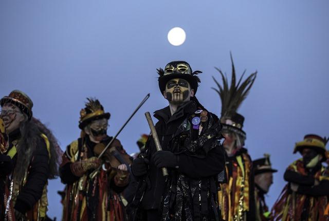 สมาชิกของกลุ่มนักเต้น Powderkeg Morris Dancers หยุดพักหลังจากการเต้นบนยอดเนินเขา Windgather Rocks ที่ไฮพีคในเมืองเดอร์บีไชร์ก่อนพระอาทิตย์ขึ้น (1 พ.ค.)