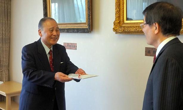 คุณฮิโร นะกะโมโต  (ซ้าย) มอบเงินบริจาค 516 ล้านเยนให้กับมหาวิทยาลัยคิวชู