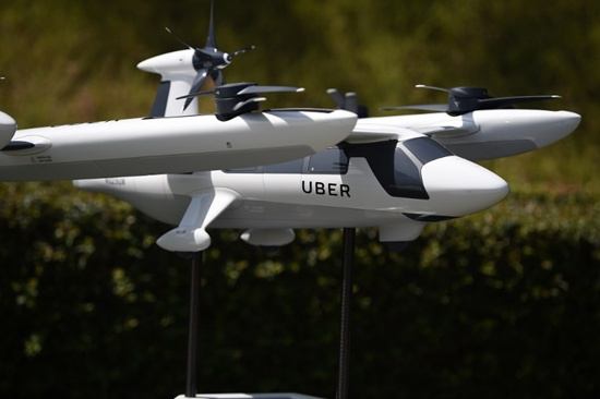 A model of Ubers electric vertical take-off and landing vehicle concept (eVTOL) flying taxi is displayed at the second annual Uber Elevate Summit, on May 8, 2018 at the Skirball Center in Los Angeles, California. Uber introduced its electric powered flying taxi vertical take-off and landing concept aircraft at the event, which showcases prototypes for UberAirs fleet of airborne taxis. Robyn Beck/AFP