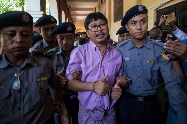 วา โลน นักข่าวรอยเตอร์ (กลาง) ถูกเจ้าหน้าที่ตำรวจควบคุมตัวมาขึ้นศาลในนครย่างกุ้ง. -- Agence France-Presse/Sai Aung Main.