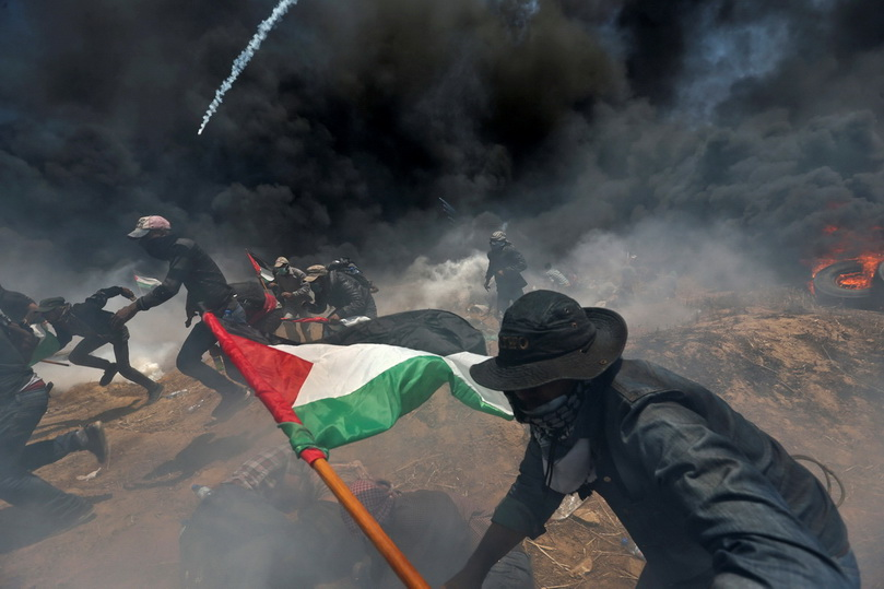 ผู้ประท้วงชาวปาเลสไตน์วิ่งหลบกระสุนและแก๊สน้ำตาที่ถูกยิงมาจากฝั่งอิสราเอล ระหว่างการชุมนุมประท้วงการย้ายสถานทูตสหรัฐฯ ไปยังนครเยรูซาเลม เมื่อวันที่ 14 พ.ค.