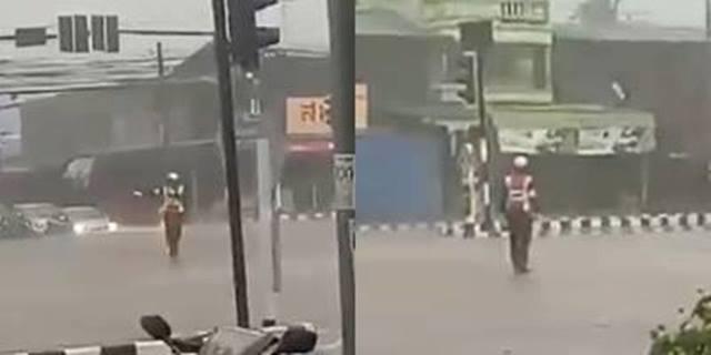 สุดประทับใจ! ตำรวจหนุ่มทุ่มสุดตัว ยืนโบกรถขณะฝนตกหนัก (ชมคลิป)