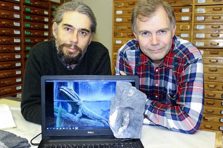 ไฟล์ภาพ ดร.โรเบิร์ต เกส (ซ้าย) และ เปอร์ อาห์เบิร์ก (Per Ahlberg) นักบรรพชีวินวิทยาสวีเดน ถ่ายภาพกับฟอสซิลตูตูเซียส และภาพวาดของเตตระพอดดีโวเนียน  (STEVEN LANG / UNIVERSITY OF THE WITWATERSRAND / AFP)