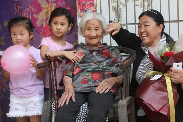 หลี่ ซิ่วจือ ถ่ายภาพกับญาติๆและเพื่อนบ้าน ในงานฉลองวันคล้ายวันเกิด 102 ปี หมู่บ้านหนันหัน อำเภอก่วงผิง เมืองหันตัน มณฑลเหอเป่ย เมื่อวันที่ 10 มิ.ย. 2018 (ภาพ ซินหวา)