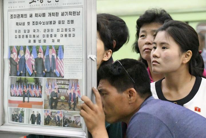 ชาวเกาหลีเหนือสนใจอ่านข่าวจากหนังสือพิมพ์ท้องถิ่นซึ่งรายงานเรื่องการประชุมซัมมิตระหว่างสหรัฐฯกับเกาหลีเหนือ ณ ที่อ่านหนังสือพิมพ์ในสถานีรถไฟใต้ดินแห่งหนึ่งของกรุงเปียงยาง  ภาพนี้ถ่ายโดยสำนักข่าวเกียวโดในวันพุธ (13 มิ.ย.)