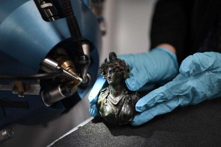 นักวิจัยใช้รังสีจากเครื่องเร่งอนุภาคออะแกลตรวจสอบรูปปั้นทองแดง (STEPHANE DE SAKUTIN / AFP)