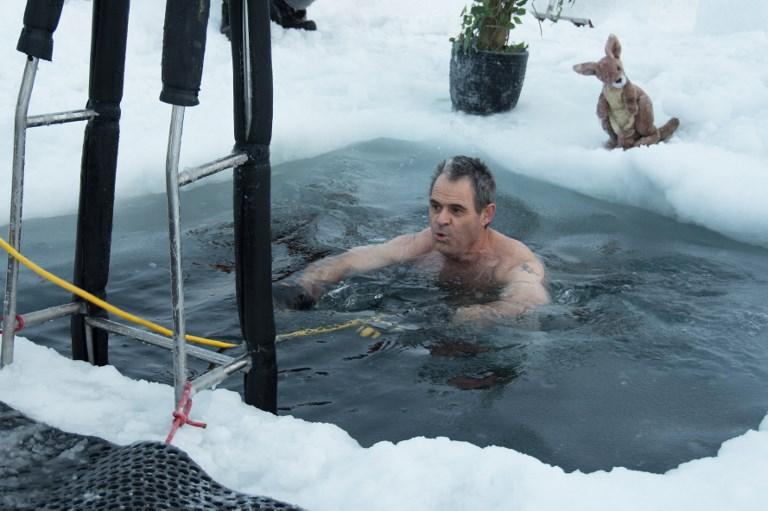 นักวิจัยประจำสถานีวิจัยแอนตาร์กติกาท้าความหนาวด้วยการถอดผ้ากระโดดลงน้ำที่อุณหภูมิต่ำกว่าจุดเยือกแข็ง (GEORGE BRETTINGHAM-MOORE / AUSTRALIAN ANTARCTIC DIVISION / AFP)