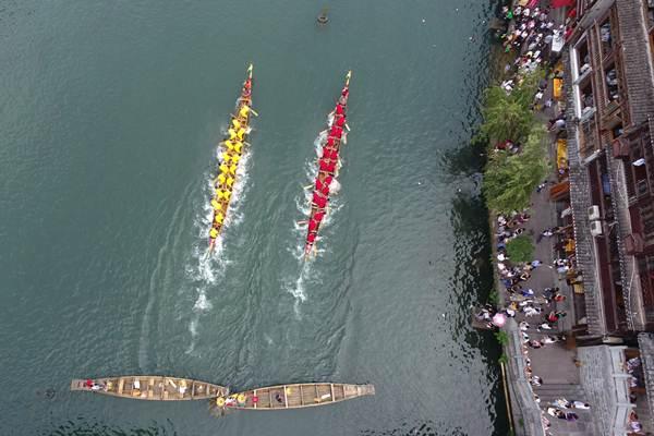 การแข่งขันเรือมังกร ณ แม่น้ำถัวเจียง เมืองเฟิ่งหวง มณฑลหูหนัน บรรยากาศเมืองโบราณท่ามกลางธรรมชาติสวยงามแห่งนี้ ยิ่งส่งให้บรรยากาศการแข่งขันเรือมังกรทรงมนต์เสน่ห์งามล้ำ ภาพวันที่ 17 มิ.ย. 2018 (ภาพ ซินหวา)