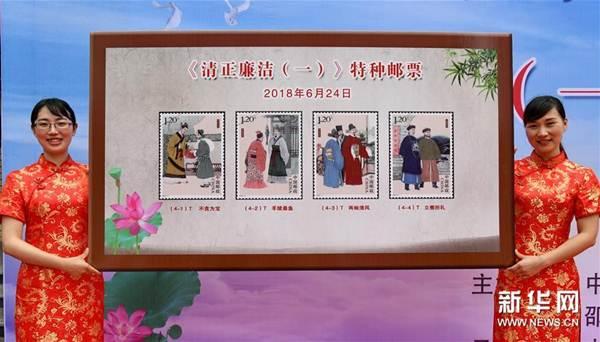 เจ้าหน้าที่เมืองเส้าอู่ มณฑลฝูเจี้ยน แสดงตัวอย่างแสตมป์ชุดพิเศษภาพขุนนางผู้ซื่อสัตย์ในยุคโบราณจีน ภาพเมื่อวันที่ 24 มิ.ย. (ภาพ ซินหวา)
