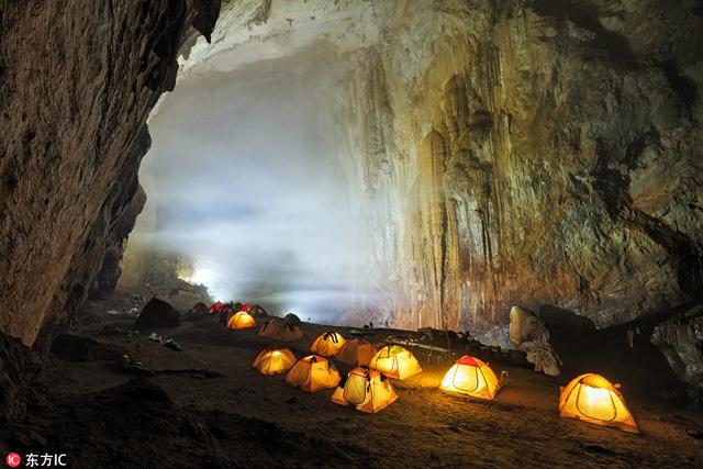 นักท่องเที่ยวกางเต็นท์ ยามค่ำคืนที่ถ้ำ Hang Son Doong ในเวียดนาม ซึ่งเป็นถ้ำขนาดใหญ่ เทียบตึกระฟ้าสูง 40 ชั้น ใหญ่จนมีและเมฆก่อตัวขึ้นภายใน (ภาพไอซี)