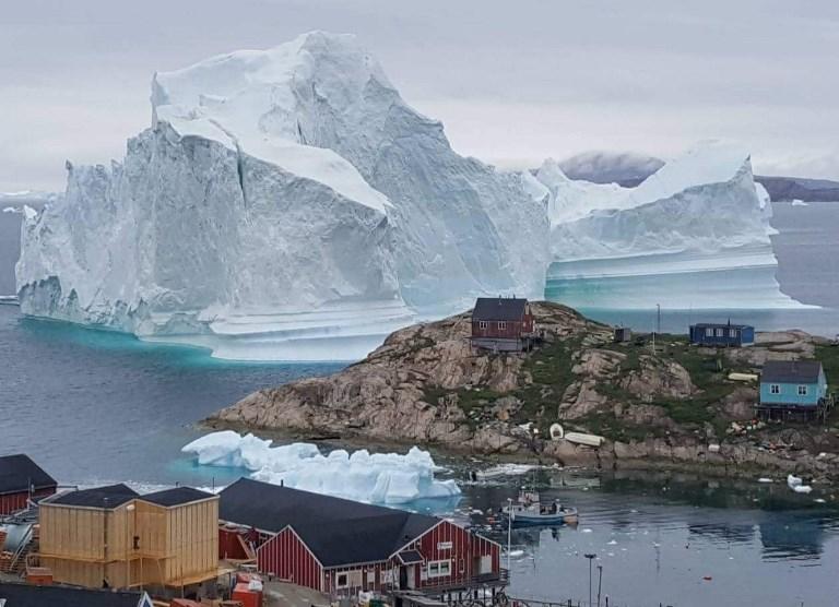 ภาพภูเขาน้ำแข็งด้านหลังหมู่บ้านที่มีผู้คนอาศัยอยู่ในอินนาอาร์ซุท (Karl PETERSEN / Ritzau Scanpix / AFP)