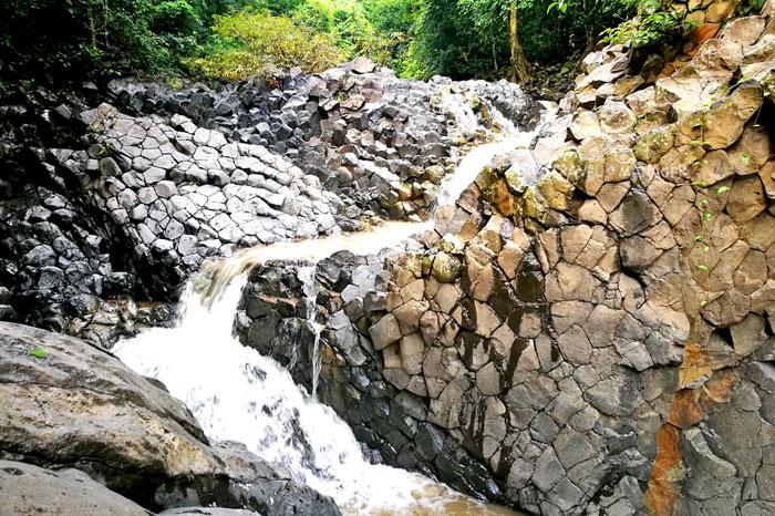 สายน้ำตกซับพลูไหลผ่านแท่งเสาหิน จากต้นน้ำลงสู่ลำธารในเบื้องล่าง