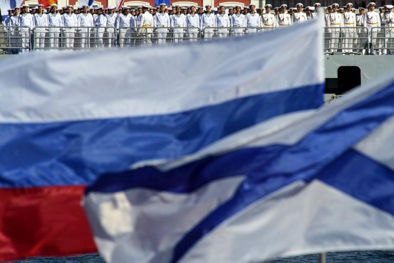 """<i>ทหารเรือรัสเซียยืนเข้าแถวบนดาดฟ้าเรือรบ """"แอดมิรัล มาคารอฟ"""" เรือฟริเกตลำหนึ่งในโครงการ 11356 ก่อนหน้าการสวนสนามในวันกองทัพเรือที่แม่น้ำเนวา บริเวณใจกลางนครเซนต์ปิเตอร์สเบิร์กวันอาทิตย์ (29 ก.ค.) </i>"""