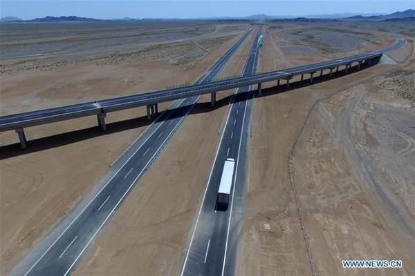 รถบรรทุกกำลังแล่นไปบนถนนทางด่วนนครหลวงปักกิ่ง-อุรุมชี เมืองเอกของซินเจียง (Beijing-Urumqi Expressway) ในฮามี (Hami) ภาพ 15 ก.ค. 2017  (ภาพ โดยซินหวา)