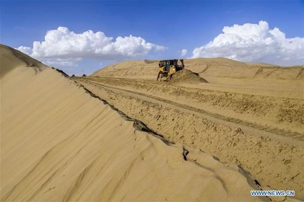 การก่อสร้างถนนในทะเลทรายเชื่อมอำเภออี๋ว์ลี่ (Yuli) กับอำเภอ เฉียมั่ว (Qiemo) ซึ่งตั้งอยู่ทางทิศตะวันออกเฉียงเหนือของเขตปกครองตัวเองชนชาติอุยกูร์มณฑลซินเจียง ภาพเมื่อวันที่ 5 ก.ค. 2018  (ภาพ โดยซินหวา)
