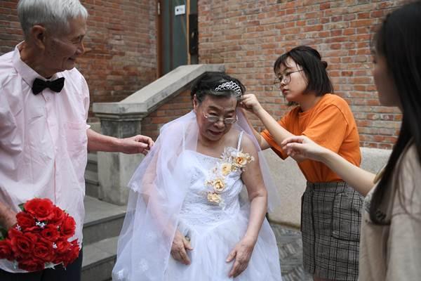 กลุ่มอาสาสมัคร กำลังช่วยเหลือผู้เฒ่าระหว่างการถ่ายภาพหมู่ ร่วมงานฉลองการแต่งงานหมู่ของกลุ่มผู้สูงอายุ ในนครเทียนจิน ฉลองวันแห่งความรักตามประเพณีจีน (ภาพ รอยเตอร์ส)