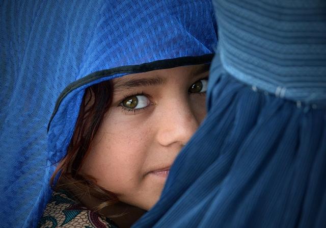 หญิงชาวอัฟกานิสถานอุ้มลูกสาวของเธอในระหว่างการเยือนของข้อหลวงใหญ่ด้านผู้ลี้ภัยแห่งสหประชาชาติ ฟิลิปโป กรันดี ที่ศูนย์ส่งกลับโดยสมัครใจอาซาเคลในเมืองนาวเชรา เมื่อวันที่ 8 กันยายน