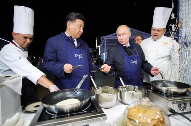 ประธานาธิบดี วลาดิมีร์ ปูติน ของรัสเซียและประธานาธิบดี สี จิ้นผิง ของจีนกำลังทำแพนเค้กในขณะเยือนงานแสดง The Far East Street นอกรอบการประชุมเศรษฐกิจตะวันออกในวลาดิวอสตอค เมื่อวันที่ 11 กันยายน