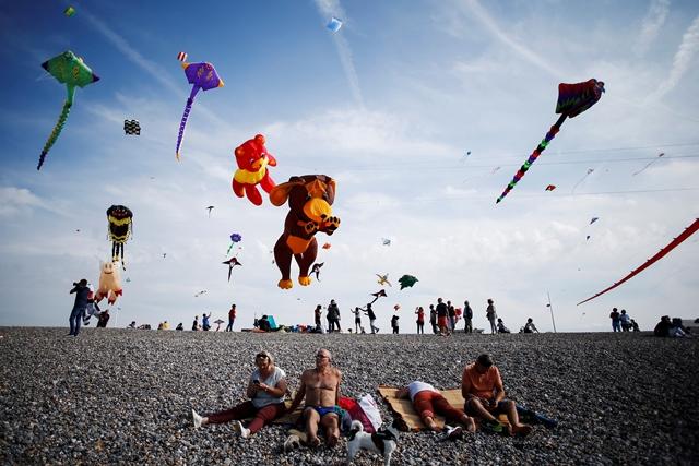 ผู้คนเล่นว่าวบนชายหาดแห่งหนึ่งขณะที่คนอื่นๆ กำลังอาบแดดในระหว่างเทศกาล International Dieppe Kite Festival ครั้งที่ 20 เมื่อวันที่ 9 กันยายน ทางตะวันตกเฉียงเหนือของฝรั่งเศส