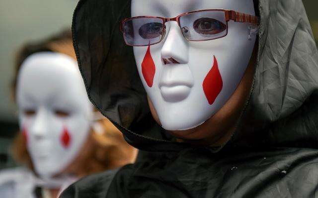 ผู้ประท้วงสวมหน้ากากเข้าร่วมการชุมนุมต่อต้านอดีตผู้บัญชาการกองทัพโคลัมเบีย มาริโอ มอนตายา นอกศาลพิเศษเพื่อความยุติธรรม (Special Jurisdiction for Peace) ในกรุงโบโกตา เมื่อวันที่ 13 กันยายน