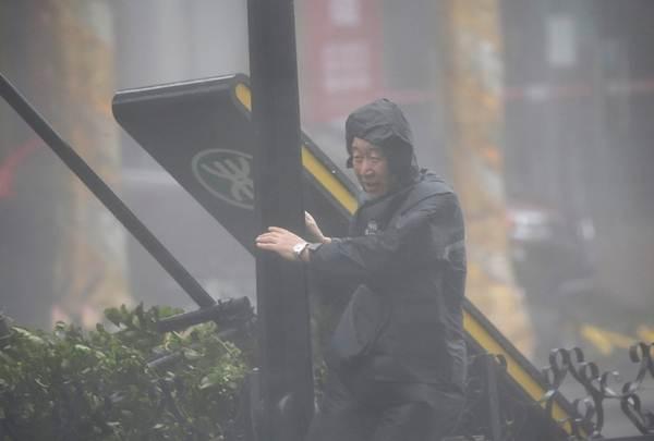 ยามรักษาความปลอดภัยเกาะเสาแน่นท่ามกลางฝนตกหนัก ขณะที่ไต้ฝุ่นมังคุดกำลังใกล้เข้ามาในวันที่ 16 ก.ย. (ภาพ รอยเตอร์ส)