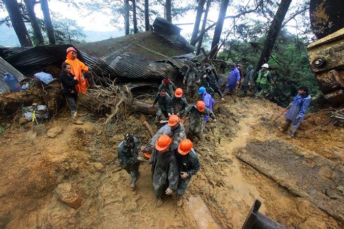 "<i>เจ้าหน้าที่กู้ภัยดึงเอาร่างของผู้ที่ติดอยู่ใต้ดินโคลนถล่มขึ้นมา ณ เขตเมืองบาเกียว ทางภาคเหนือของกรุงมะนิลา เมื่อวันอาทิตย์ (16 ก.ย.) ทั้งนี้เกิดดินโคลนถล่มในหลายบริเวณทางภาคเหนือของฟิลิปปินส์ ทำให้มีผู้เสียชีวิตไปอย่างน้อย 64 คน เนื่องจากฝนตกกระหน่ำจากฤทธิ์พายุไต้ฝุ่น ""มังคุด"" </i>"