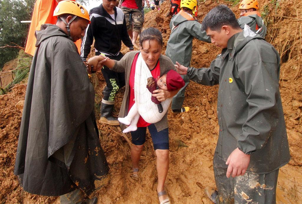 "<i>เจ้าหน้าที่กู้ภัยช่วยเหลือแม่และบุตรน้อยของเธอ ขณะทั้งสองอพยพออกมาอยู่ในพื้นที่ปลอดภัยกว่า ภายหลังดินโคลนถล่มในเขตเมืองอิโตกอน จังหวัดเบงเกต ทางภาคเหนือของฟิลิปปินส์ เมื่อวันอาทิตย์ (16 ก.ย.) สืบเนื่องจากไต้ฝุ่น ""มังคุด"" </i>"